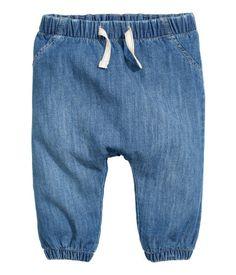 Denimblå. Ett par dra-på-byxor i mjuk bomull. Byxorna har resår i midjan med dekorativt knytband fram. Fuskfickor fram och resår vid bensluten. Trikåfodrade
