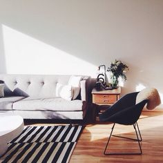 Great simple, monochromatic interior with black and white striped rug and tufted couch.