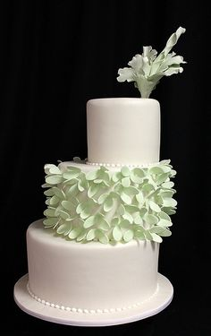 dramatic flower wedding cake...  offset three tier fondant cake with mint green flowers. Find all your wedding planning needs at www.brides-book.com