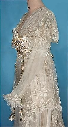 Edwardian ecru satin and lace wedding gown, liberally adorned with wax orange blossoms. The long sleeves are sheer tulle (edged at the wrists with ruffled & appliqued lace) which flow out from under the capped over sleeve. The lace cascades down the length of the skirt in elegant layers.