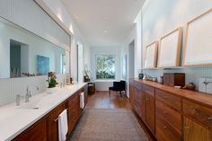 In this modern master bathroom, there's wood cabinetry for plenty of storage, a double-sink vanity and the bath is positioned beneath a window at the end of the room.