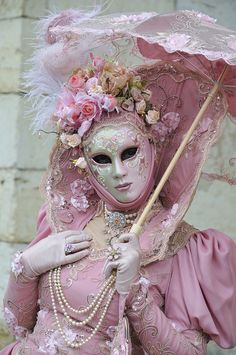 A pretty sort of ashes of roses costume with a beautifully painted mask.