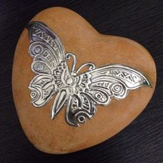 Pewter butterfly on a stone heart by Heather van den Bergh