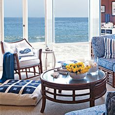 Elegant water-resistant fabrics, pillows, and blankets inspire connection with the sea and can handle this cottage's heavy traffic | Coastalliving.com