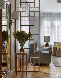 Перегородка между гостиной и коридором выполнена из древесины дуба на основе подобранного дизайнером графического орнамента. Занавески выполнены из испанских тканей.