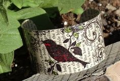 Cuff bracelet made of old book pages, a metal cuff, stamps and some tipped in colors.