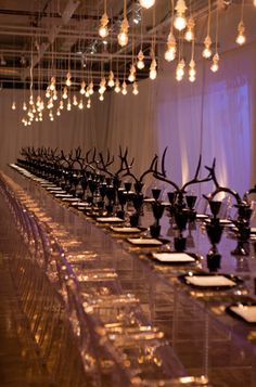 Modern and moody this austere design gives breathing room to every gorgeous detail. Ghost chairs and acrylic tables open the space while rows of mercury bulbs provide illumination to the dramatic black tableware and accents. Antler Centerpiece, Ghost Chairs, Bravo Tv, Dramatic Lighting, Light Side, Party Props, Party Ideas, Art Deco Wedding, Wedding Events