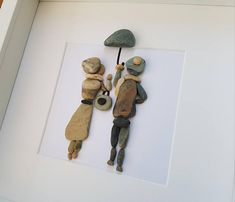 A beautiful and unique romantic handmade beach pebble art picture of couple walking in the rain. This picture is a lovely home decoration and would make a perfect gift. The picture is made using pebbles. All materials are carefully placed and fixed with high strength glue onto high