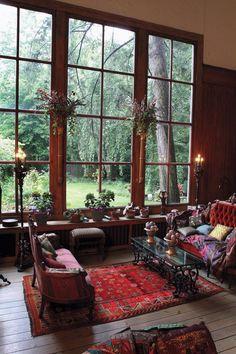 Intérieur salon style bohémien avec canapés, tapis, grande baie vitrée et lumières