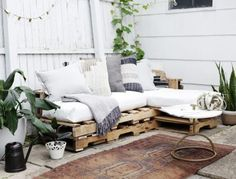 Pallet Outdoor Furniture Wood pallet couch on patio with white cushions and throw pillows. - This article will show you the steps, materials and tools you need to create an L-shaped couch using pallet wood and how to make no sew cushions. Wood Pallet Couch, Pallet Patio Furniture, Outdoor Furniture Plans, Wood Pallets, Pallet Benches, Pallet Tables, Pallet Bar, 1001 Pallets, Recycled Pallets