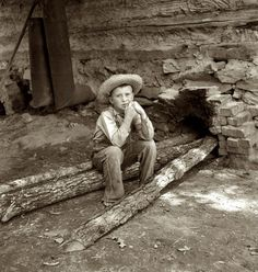 """July 1939. """"10-year-old son of tobacco sharecropper can do a 'hand's work' at harvest time."""" Seen here feeding logs into the fire next to flue of the curing barn. Granville County, North Carolina. by Dorothea Lange for the Farm Security Administration."""
