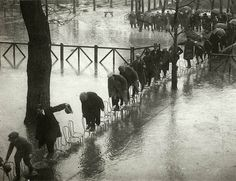 People in Paris avoid getting wet in the flood by stepping on a series of chairs in 1924.