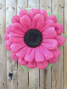 "This Pink Burlap Daisy Wreath is made using water resistant poly burlap mesh, with a Black wood chip center and Measures 21"" in diameter (with leaves) or 18 without, 4"" in depth and will fit between your front door and storm door. This Wreath is bright, cheery and would look great on any door! All"