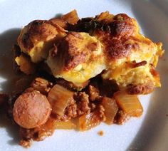 Chili Cheese Dog Bake 1 yellow onion, diced 1 pound ground beef ½ teaspoon salt ½ teaspoon pepper ½ cup tomato sauce ½ cup ketchup 2 ½ tbsps chili powder ½ teaspoon sugar 10 hot dogs 1 can pre-made biscuits 4 tablespoons butter, melted ½ teaspoon garlic powder 2 tablespoons parsley 1 cup shredded cheddar cheese