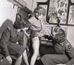 Women's Royal Army Corps member showing new tattoo on her leg to fellow enlistees. WWII.