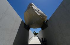 Visitors walk underneath ''Levitated Mass,'' a permanent exhibit at the Los Angeles County Museum of Art. Created by artist Michael Heizer, it features a 340-ton boulder. Photo by Kevork Djansezian/Getty Images.