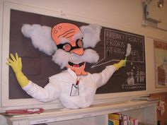 That's a real shirt, with real pencils in the pocket, and real rubber gloves, with a real test tube. The hair and steam is cotton batting. The background is black construction paper - doesn't it look like a blackboard?   Who knows WHAT those goggles are made of but I sure am glad that he's following proper lab precautions! Safety first! Chemical explosions second.  At an Upper West Side branch of the New York Public Library.