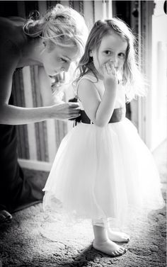 Mom tying bows for flower girls