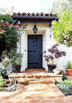 Charming Spanish-inspired home exterior with succulent landscaping, hanging iron lantern and painted black front door.