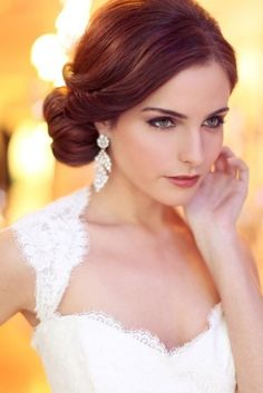 Elegant bride in a lace gown with simple hair and vibrant jewelry.