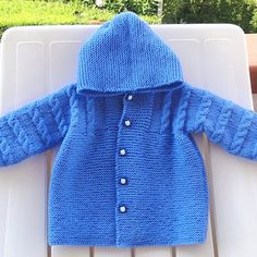 A knitted blue jacket with buttons down the front and an attached hood