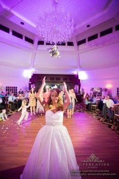 Who do you think caught the bouquet? Bride tossing the bouquet to guests, beautiful #purpleuplighting in the background. DIY and get the look at http://RentUplights.com