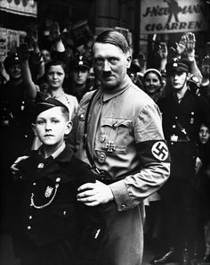 Hitler poses with a boy of the Hitler Youth.