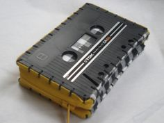 Up for auction on Tophatter  Sunday May 13 @ 12pm Central time    Repurposed cassette tape. Handmade and completely unique. Carry your cash and plastic in style! Can be used as a wallet, coin purse or I've even used it as a camera case. Fits neatly and comfortably in your back pocket.     Black cassette, yellow zipper, black & white gingham inner lining.