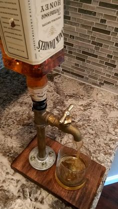 A handmade brass pipe fitting drink dispenser. Self venting head commonly used in bars and fits most liquor bottles for easy changing between drinks. Live edge base with bark and walnut stain. *There is an air vent tube that can be inserted into the bottle for smooth pouring which eliminates the need to have a vented bottle, making changing drinks easier to do.