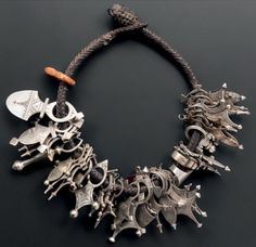Africa | Collection of silver alloy, white metal and stone pendants from the Tuareg people. All strung on a leather strap, woven using basketry technique