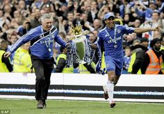Carlo Ancelotti (left) and Florent Malouda celebrate with the 2009/10 trophy after defeating Wigan at Stamford Bridge