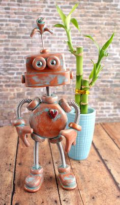 Pembro Patina Plant Guard Robot Sculpture.   What the heck is a Patina Robots? A: Bots designated to stand guard by your house plants, bravely protecting them from bugs, pets, unwanted fingers and most importantly, looking adorable. Patina Bot can also be an awesome gift for the geeky plant lover or robot fan in your life., $60.00