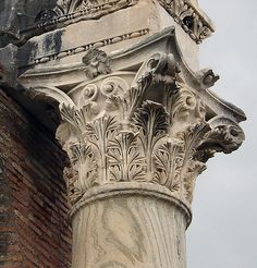 """A well-preserved Roman Corinthian capital in situ at the frigidarium of the Forum Baths, Ostia (I, XII, 6). The date of the capital is ca. 160 CE. Pensabene refers to this as an example of Corinzio Asiatico (""""Asiatic Corinthian,"""" Scavi di Ostia VII, cat. no. 333). The lobes of the individual acanthus leaves are sharply-cut, almost prismatic in layout. Height: 87 cm Material: imported Pentelic marble (column shaft is of green-veined cipollino)."""