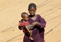 A Somali refugee girl carrying her sibling walks outside their tent at the Ifo Extension refugee camp in Dadaab, near the Kenya-Somalia border October 19, 2011. REUTERS/Thomas Mukoya