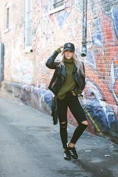 Jaqueta de couro preta, suéter verde, calça preta rasgada no joelho, tênis preto Adidas.