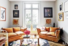 Midcentury living space with two sofas, neutral and blue rug, and major art collection on walls