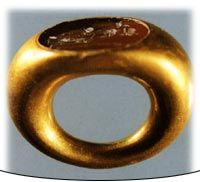 Anatolia Gold and Korneol 	The 1st century BC-1st century AD The section of the ring is round. Flat cut korneol is placed in the oval slot. The figure of a woman standing on a stone is placed. She carries a cornucopia in her left hand and staff in her right hand. She can be Felicitas because she seems to lean against something.