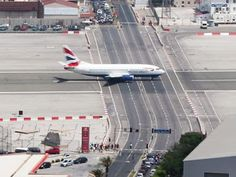 A plane taxis down the runway in Gibraltar, crossing between stopped traffic. - photo from Aviação no Brasil e no Mundo;  A major road intersects with the runway at the airport in Gibraltar.