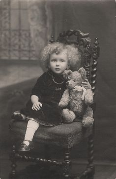 Little curly topped girl with teddy bear.