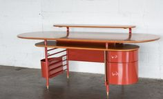 This 'Johnson Wax 1' desk was originally designed by Frank Lloyd Wright in  1936 for the S.C. Johnson Company's Administrative Building in Racine,  Wisconcin. The Frank Lloyd Wright Foundation gave Cassina the right to  produce it in 1985 (it is no longer manufactured). This particular desk is  marked Cassina #0147, Frank Lloyd Wright. It has three cherry wood tops  positioned at different heights and a 'brick red' painted tubular steel  frame. It includes two drawers and a removable waste ...