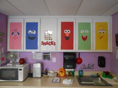 sesame street theme decor on cabinet doors, just construction paper, cut out eyes noses and mouths, easy project, easy to recognize,  Toddler, preschool daycare classroom.