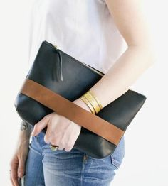This clutch is made to carry all of your essentials. Hand cut from a soft yet sturdy 5 oz. oil hide leather, the unlined clutch features a hand strap and solid brass black YKK zipper.