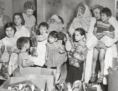 Marion Davies ( second adult from the right) at a Cristmas party that she sponsored every year for the children being cared for at her children's clinic in 1954.