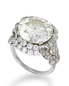 A diamond single-stone ring, circa 1935  The old brilliant-cut diamond, weighing 10.05 carats, between a double border of brilliant-cut diamonds, to a scrolling openwork gallery set with single and old brilliant-cut diamonds, remaining diamonds approximately 1.55 carats total
