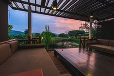 Gorgeous tropical lanai deck with pergola and cushioned outdoor furniture.
