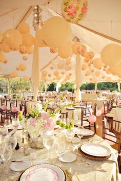 Tons of white and floral paper lanterns in this tent make for sophisticated wedding decor