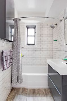 """""""I had basic white subway tiles in mind from the start and chose a porcelain floor tile with a faux-wood finish in a large, modern size. I fit in new under-sink storage with Ikea's Godmorgon glossy gray bathroom vanity and also added a wall-mounted cabinet facing the vanity and beveled medicine cabinet."""" - Rima"""