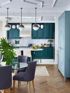 Contemporary kitchen features peacock blue cabinets paired with black countertops and a marble slab backsplash.