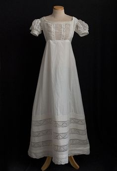 Embroidered white cotton dress, early 1820s. This dainty dress anticipates the change from the Neoclassical to the Romantic period. The waist is still high as in the Empire style, but the skirt is flared and fuller in our dress. The bodice and sleeves have alternating rows of sheer ruched cotton mull and hand-embroidered eyelet. Bands of eyelet alternating with rows of trapunto cording form a wide hem border both decorative and functional.