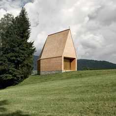 The steeply pitched roof of this shingled chapel by Bernardo Bader Architects provides a dramatic worship space, which narrows towards a small window facing a grassy hillside in western Austria.